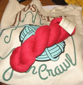 Example skein of the red linen yarn resting on the Rose City Yarn Crawl bag.
