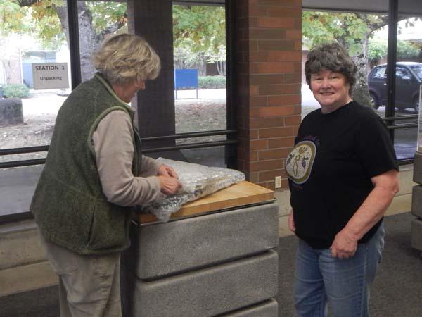 Super volunteer Mary Elle helping unpack a painting.